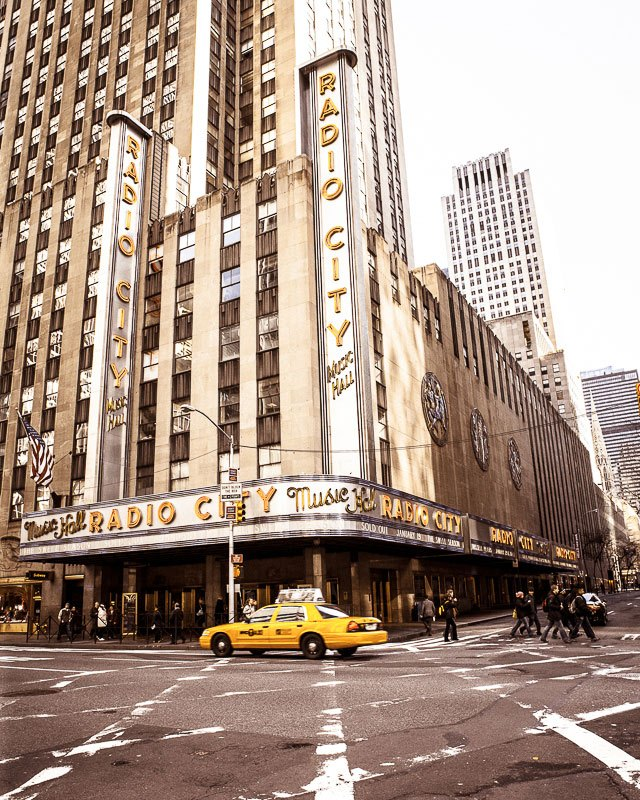 A wall art photo of a yellow taxi going by Radio City Hall in New York