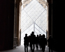 wall art of people walking towards the glass pyramid of the Louvre