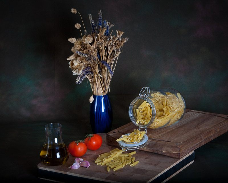 Still life wall art of pasta, tomatoes, olive oil and garlic