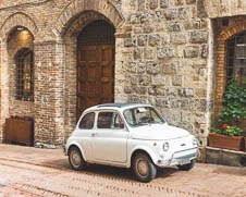 Classic Fiat 500 mini packed outside a restaurant in Tuscany