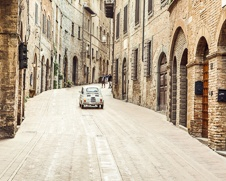 Classic Fiat 500 mini driving through an alley way in Tuscany
