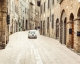 Art print of a classic Fiat 500 mini driving through an alley way in Tuscany